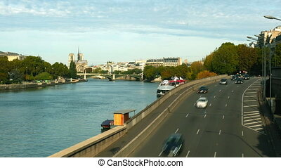 Time lapse of car traffic on the Seine river embankment in Paris and distant Notre-Dame Cathedral, France