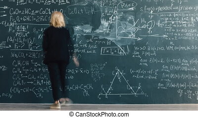 Time lapse of clever lady professor writing formulas in ...