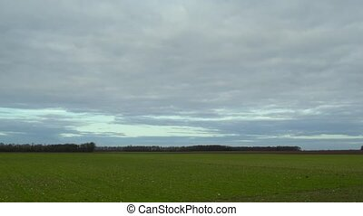 Time lapse of clouds moving quickly over green field
