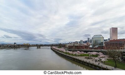 Time lapse of clouds over Portland OR city with flowering Cherry Blossom Trees