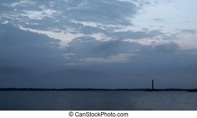 Time lapse of daybreak over water with lighthouse and clouds