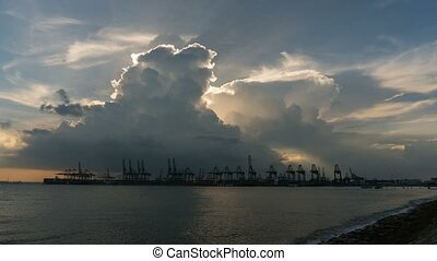 Time lapse of dramatic clouds over shipyard with cranes along Singapore Straits at sunset