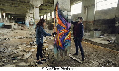Time-lapse of graffiti artists are using aerosol paint to decorate abandoned industrial building with modern graffiti images. Creativity, street art and people concept.