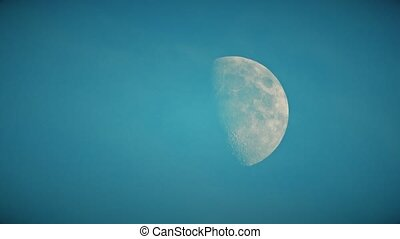 Time lapse of half moon and clouds or smoke, telephoto lens...