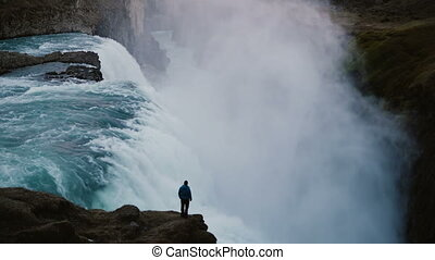 Time lapse of landscape of the Gullfoss waterfall in Iceland and man standing on edge of the cliff, enjoying the view.