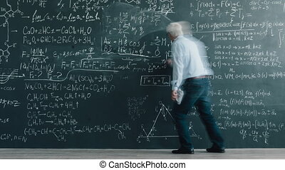 Time lapse of mature man in casual clothing writing formulas...
