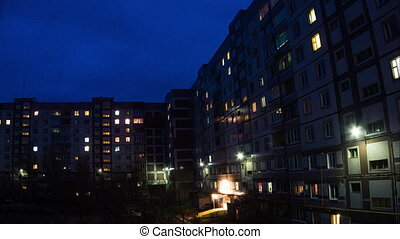 Multi-storey houses, in apartments that light up windows. Timelapse. Day to Night. ULTRA HD 3840 x 2160. 30fps