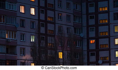 Time lapse of multistorey building with changing window lighting at night.