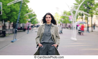 Time lapse of pretty girl standing in street hands in pockets looking at camera