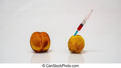 time lapse of rotting peach with a syringe, the concept of the harm of drug addiction and the detrimental effect of bad habits on the body.