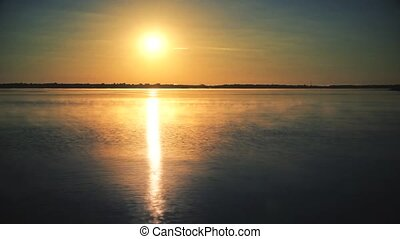 Time lapse of sun rising over water at dawn with morning mist