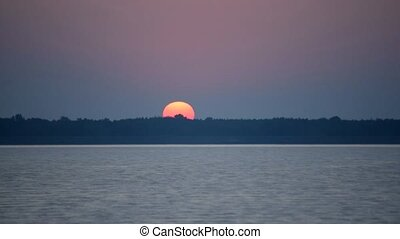 Time lapse of sunrise in clear sky over water and forest