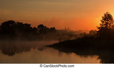 time lapse of Sunrise over river, landscape, fog running over the river, church on the background