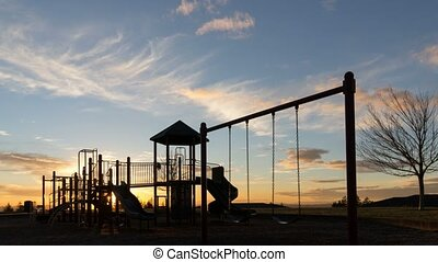 Time lapse of sunset and clouds over playground 4k uhd