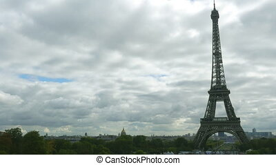 Time lapse of the Eiffel tower against partly cloudy sky -...