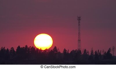Time lapse of the sun setting behind cell tower