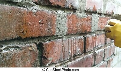 Time lapse of woman pointing brick wall with mortar.