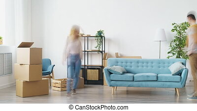 Time-lapse of young couple man and woman bringing boxes and furniture to empty house relocating decorating interior then relaxing on couch together.