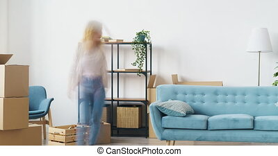 Time lapse of young family husband and wife relocating to new house bringing furniture and belongings then resting on sofa together in cozy room