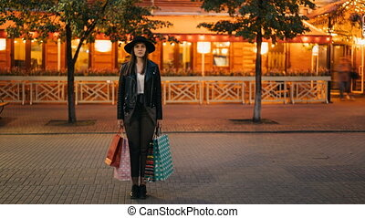 Time-lapse of young woman shopaholic standing outdoors in the street with shopping bags and looking at camera while flow of people is moving around her.