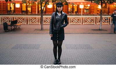 Time-lapse portrait of serious Asian woman in stylish clothes standing in the street in the evening and looking at camera when crowds of men and women are passing by.