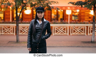 Time-lapse portrait of tired Asian girl towny standing in pedestrian street with hand in pocket and looking at camera then leaving, men and women are whizzing around.