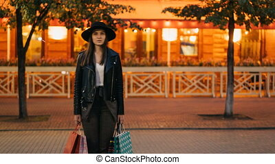 Time-lapse portrait of tired female shopper beautiful woman standing with paper bags in the street and looking at camera while people are moving around in hurry.