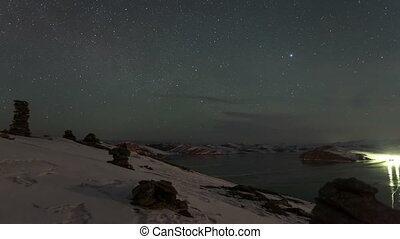 Time lapse rotating stars above mountain