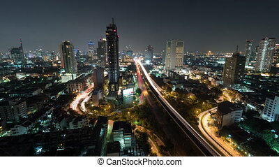 Time lapse shot of night life in the big city, lighted skyscraper, traffic, intersection, Bangkok, Thailand