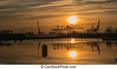 time-lapse sunrise in the port of Valencia cranes working...