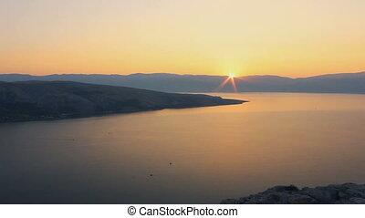 Time lapse sunrise on sea with mountain