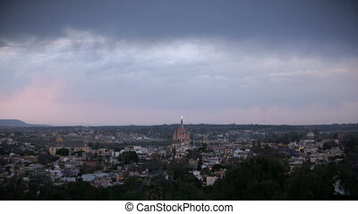 Timelapse sunset of San Miguel de Allende and it's historic church located at the Parroquia de San Miguel Arcangel, Mexico with fast moving clouds overhead