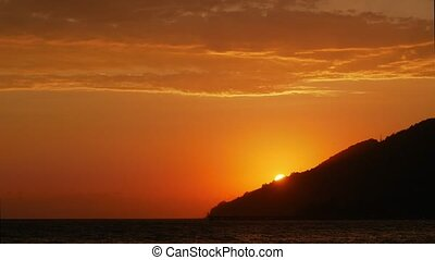 Time Lapse. The sun goes over the mountain at sunset. View from the sea shore