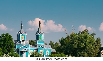 Krasnyy Partizan, Dobrush District, Gomel Region, Belarus. Time Lapse, Timelapse Old Wooden Orthodox Church of the Nativity of the Virgin Mary At Sunset In Village. Zoom Out