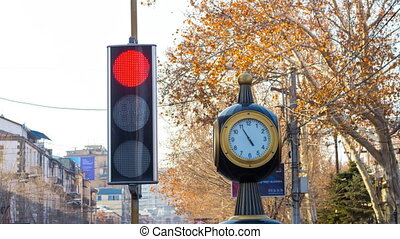 Time lapse: traffic lights with a clock on the city background with trees