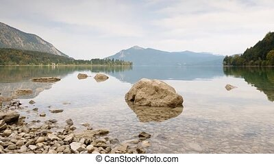 Time Lapse video of stone in water of mountain lake. Gentle waves on autumn lake, forest islands and high mountains in background.