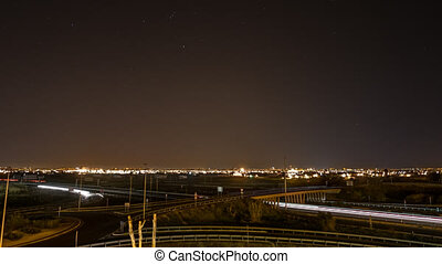 Time lapse with car trails, city skyline and stars
