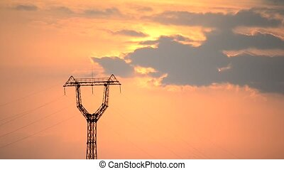Time lapse with transmission tower and cumulus clouds at dawn