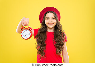 time. little girl in french style hat. happy girl with long curly hair in beret. beauty hairdresser. child with alarm clock. Timeless fashion. parisian child on yellow. good morning. morning grooming