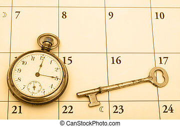 A pocket watch and a key on a calendar background, time management