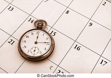 Time Management - A pocket watch sitting on a calendar...