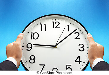 Time management. - Businessman holding a wall clock.