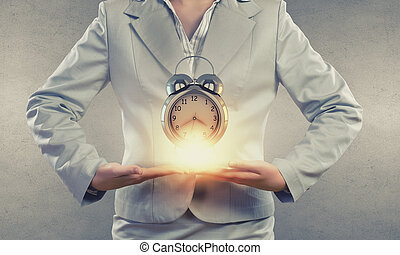 Time management - Close up of businesswoman holding in hands...