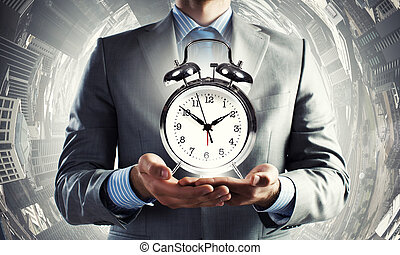 Close up of man holding alarm clock in the hands
