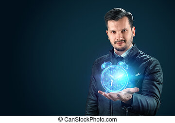 Time management concept, businessman holds a hologram of an alarm clock, clock on his hand. Hourly poes, passage of time, dead line. Copy space.
