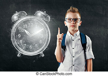 Time management concept, schoolboy with a backpack and near the image of an alarm clock. Time is fleeting, dead line, the passage of time, children's time. Copy space.