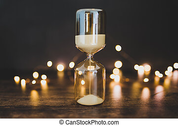 time management hourglass surrounded by fairy lights bokeh...