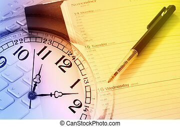 Time management - Pen, diary, clock and computer keyboard