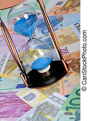 Time of money. A sand-glass and the European currency