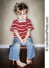 Time Out - A young boy sits on his time out chair